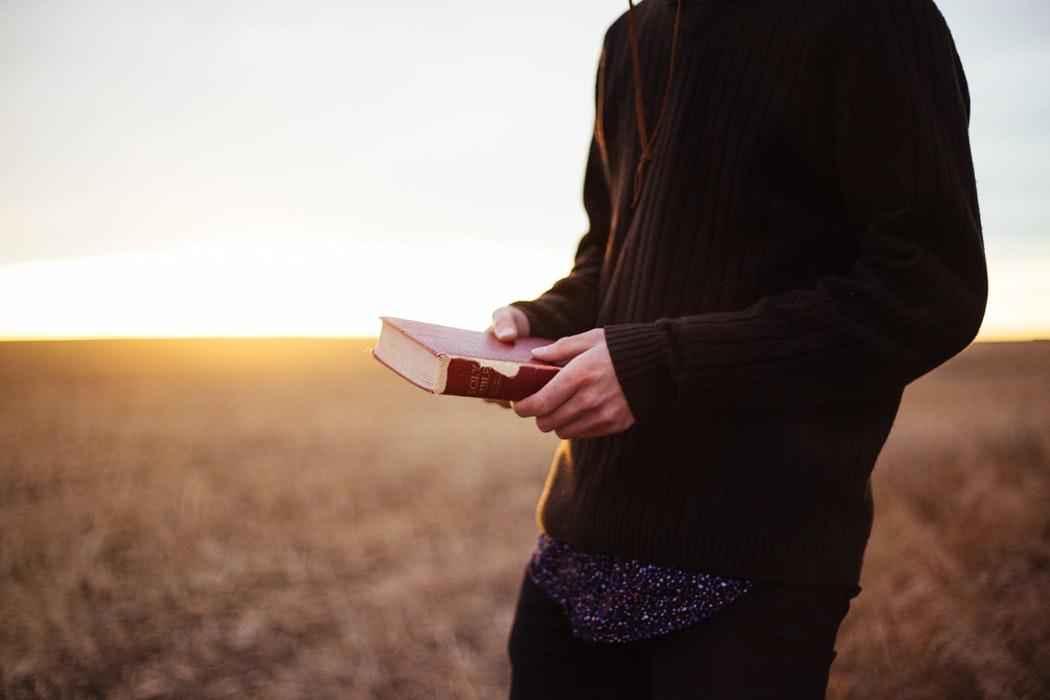 Man holding Bible walking in field